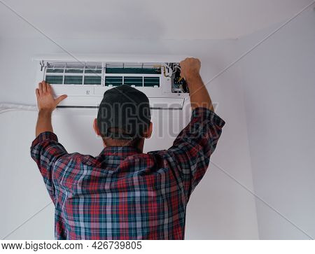 Service And Maintenance Of The Air Conditioner. A Young Male Technician Is Cleaning And Replacing Th