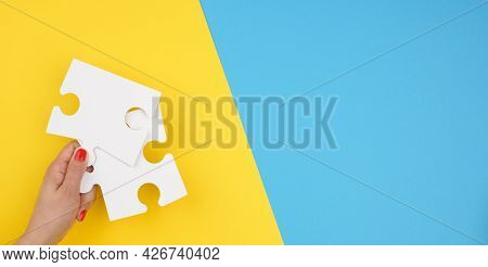 Female Hand Holds A Fragment Of A White Large Puzzle On A Blue Background, The Concept Of Finding An