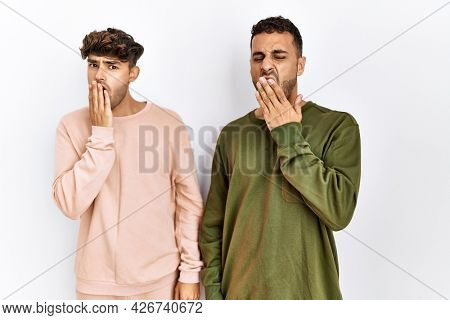 Young gay couple standing over isolated white background bored yawning tired covering mouth with hand. restless and sleepiness.