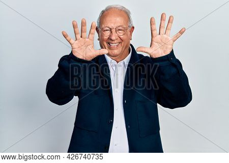 Senior man with grey hair wearing casual style and glasses showing and pointing up with fingers number ten while smiling confident and happy.