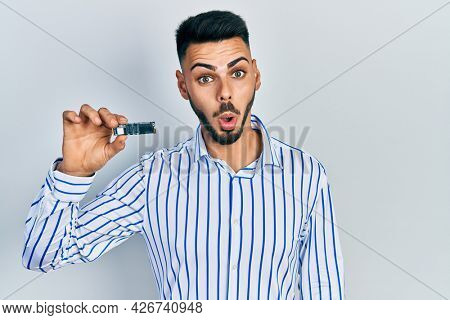 Young hispanic man with beard holding ssd memory scared and amazed with open mouth for surprise, disbelief face