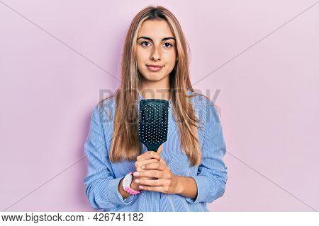 Beautiful hispanic woman holding hairbrush thinking attitude and sober expression looking self confident