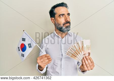 Middle age man with beard and grey hair holding south korea flag and won banknotes smiling looking to the side and staring away thinking.