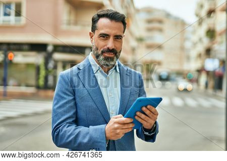 Middle age businessman smiling happy using touchpad at the city.