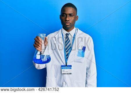 Young african american man wearing scientist uniform holding test tube thinking attitude and sober expression looking self confident