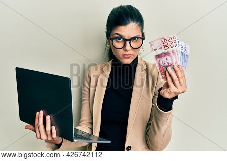 Young hispanic woman wearing business style holding laptop and swedish krone skeptic and nervous, frowning upset because of problem. negative person.