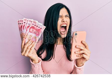 Young hispanic woman using smartphone holding chinese yuan banknotes angry and mad screaming frustrated and furious, shouting with anger. rage and aggressive concept.