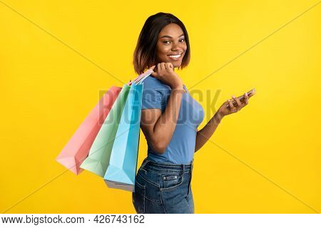 Black Woman Using Phone Posing With Shopper Bags, Yellow Background