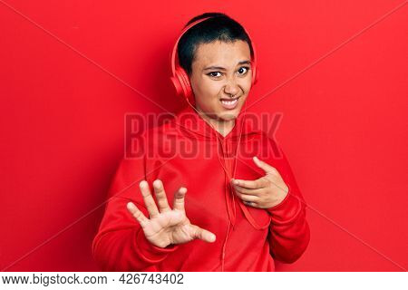 Beautiful hispanic woman with short hair listening to music using headphones disgusted expression, displeased and fearful doing disgust face because aversion reaction. with hands raised