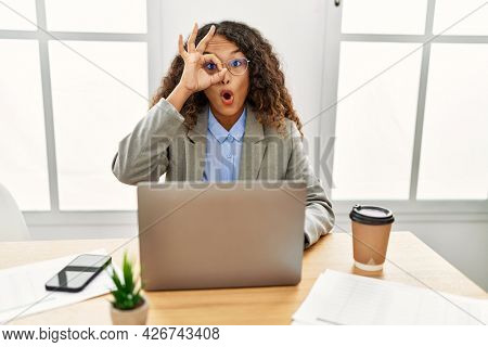 Beautiful hispanic business woman sitting on desk at office working with laptop doing ok gesture shocked with surprised face, eye looking through fingers. unbelieving expression.
