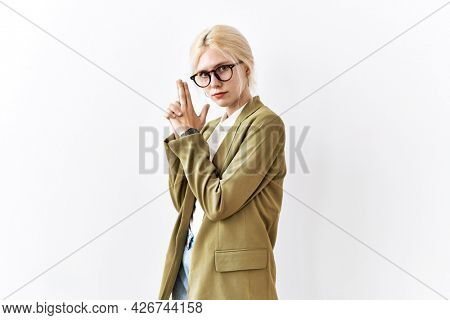 Beautiful caucasian business woman standing over isolated background holding symbolic gun with hand gesture, playing killing shooting weapons, angry face