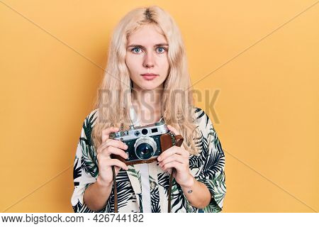Beautiful caucasian woman with blond hair holding vintage camera relaxed with serious expression on face. simple and natural looking at the camera.