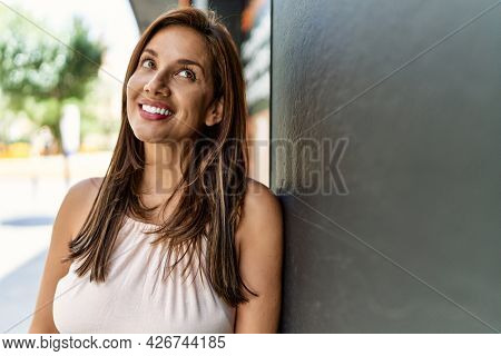 Hispanic beautiful woman standing outdoors smiling happy on a sunny day leaning on the wall