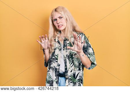 Beautiful caucasian woman with blond hair wearing tropical shirt disgusted expression, displeased and fearful doing disgust face because aversion reaction. with hands raised