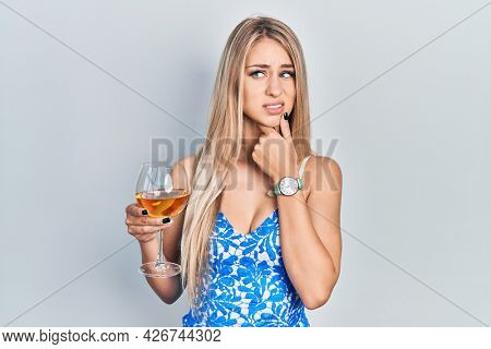 Young beautiful caucasian woman drinking a glass of white wine thinking worried about a question, concerned and nervous with hand on chin