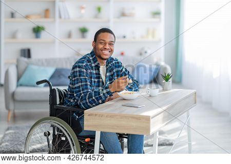 Cheerful Impaired Black Guy In Wheelchair Having Breakfast, Eating Tasty Cereal At Home
