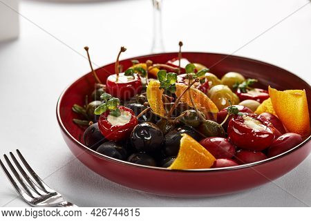 Pickled Vegetables In A Plate, Olives, Black Olives, Stuffed Peppers, Radishes. Assorted Vegetables,