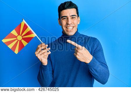 Handsome hispanic man holding macedonian flag smiling happy pointing with hand and finger