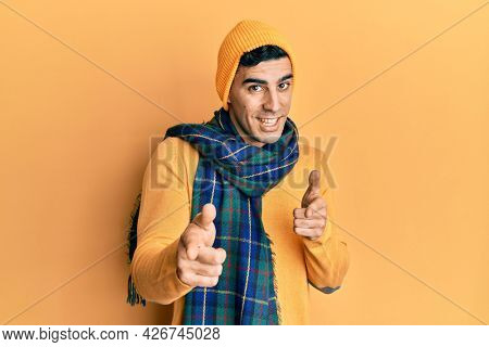 Handsome hispanic man wearing wool hat and winter scarf pointing fingers to camera with happy and funny face. good energy and vibes.
