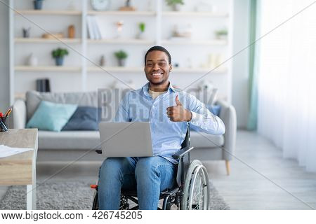 Portrait Of Happy Handicapped Black Guy With Laptop Showing Thumb Up Gesture, Smiling At Camera Indo