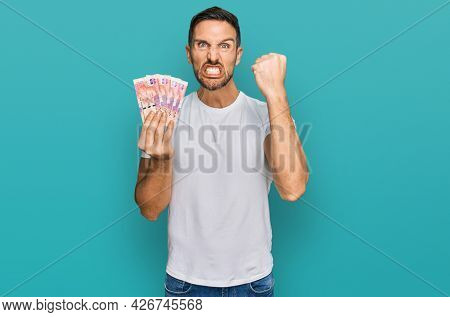 Handsome man with beard holding south african 50 rand banknotes annoyed and frustrated shouting with anger, yelling crazy with anger and hand raised