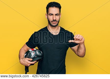 Hispanic man with beard holding motorcycle helmet with angry face, negative sign showing dislike with thumbs down, rejection concept