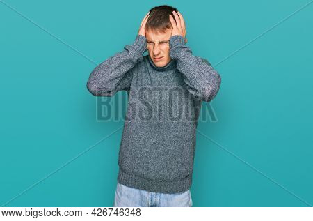 Young blond man wearing casual clothes suffering from headache desperate and stressed because pain and migraine. hands on head.