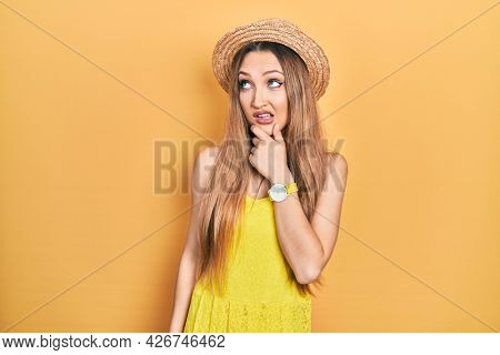 Young blonde girl wearing summer hat thinking worried about a question, concerned and nervous with hand on chin