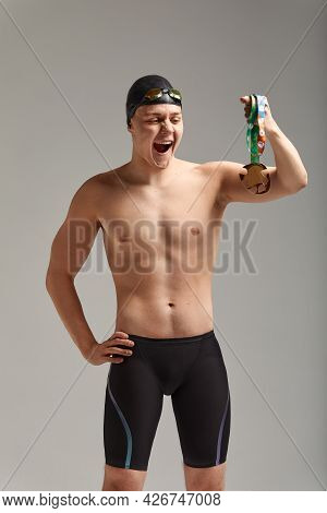 Athlete Swimmer With A Medal In His Hands Celebrating A Victory, Gray Background, Copy Space