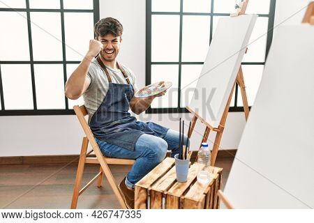 Young hispanic man painting at art studio annoyed and frustrated shouting with anger, yelling crazy with anger and hand raised