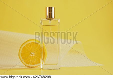 Citrus Scent, Perfume With Lemon Scent Concept, Lemon Slice And Bottle Of Perfume On Yellow Backgrou