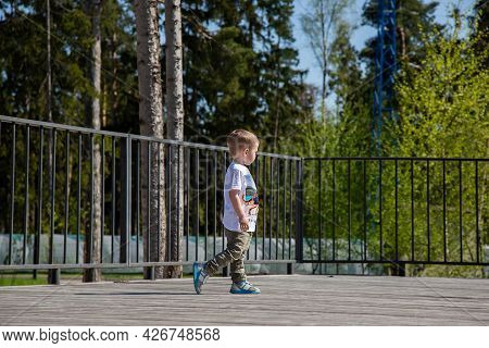 Caucasian Little Boy Walks Through The Territory Of The Playground Outdoors On A Sunny Day.