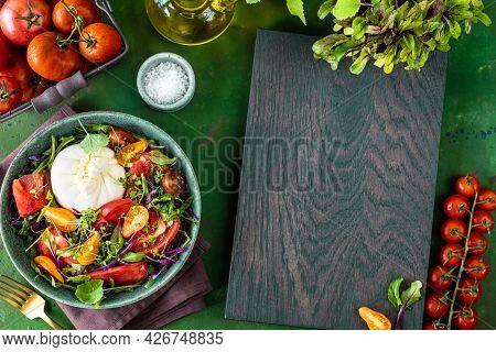Salad With Tomatoes, Arugula, Burrata Cheese And Microgreens On A Green Stone Background, Top View.