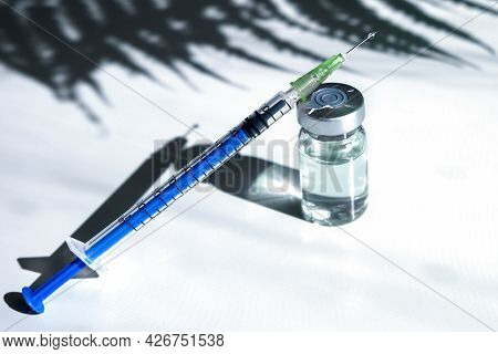 A Glass Ampoule With A Clear Liquid With A Syringe. Syringe Next To The Ampoule. Botox Glass Medicin