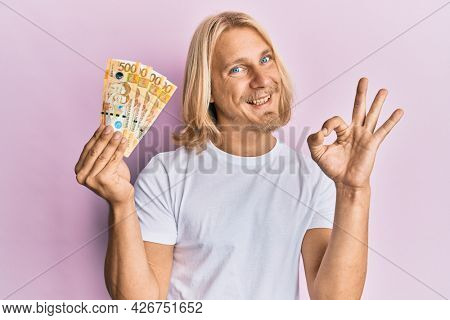Caucasian young man with long hair holding 500 philippine peso banknotes doing ok sign with fingers, smiling friendly gesturing excellent symbol