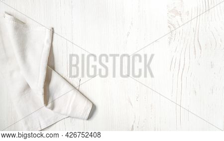 White Linen Napkin On Wooden Background With Copy Space. Top View Flat Lay. Kitchen Napkin On White