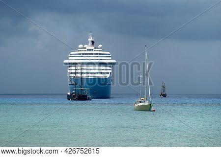 Different Size Ships Under The Heavy Sky Drifting Near Grand Cayman Island (cayman Islands).