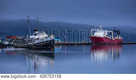 Old Black Ship And New Red Ship Anchored In Beagle Channel Waters In Ushuaia, Tierra Del Fuego, Arge