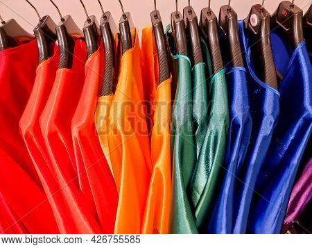 Rainbow Colors. Choice Of Casual Clothes On Black Hangers, Isolated On White.variety Of Silk Dresses
