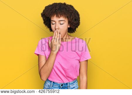 Young hispanic girl wearing casual clothes bored yawning tired covering mouth with hand. restless and sleepiness.