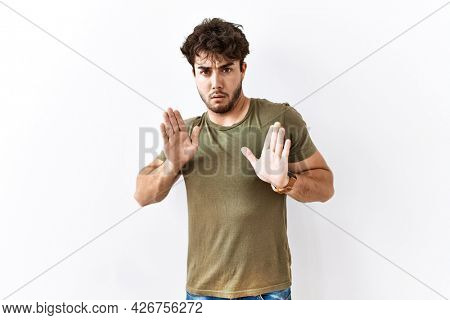 Hispanic man standing over isolated white background moving away hands palms showing refusal and denial with afraid and disgusting expression. stop and forbidden.