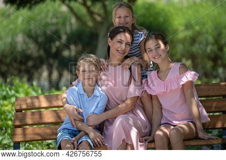 Happy Mother and Her Three Precious Kids Spending Weekend Together Outdoors. Family Time in City Park on Summer Day. Love Concept.
