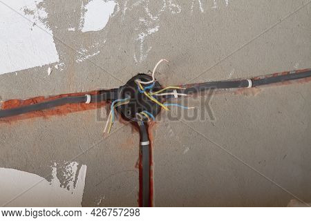 The Electrical Box With Wires Is Mounted In The Wall, The Bare Wires Stick Out To The Sides.