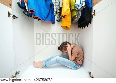 Unhappy Boy Hiding In The Wardrobe. Domestic Violence And Abused Concept. Unhappy Childhood.