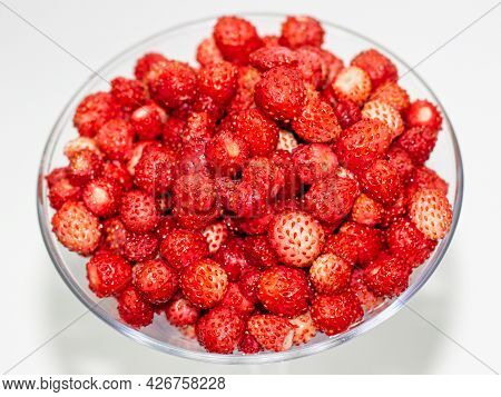 Ripe Red Wild Strawberry In A Glass Dish Against Light Background. Selective Focus, Top View