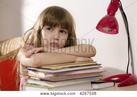 Unhappy Little Girl Studying At The Desk