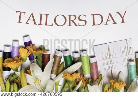 Greeting Card With Multi-colored Threads And The Text Tailors Day. For The Holiday Of A Seamstress,