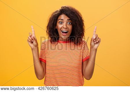 Amazed Happy Enthusiastic Cute African American Woman With Curly Hairstyle In Striped T-shirt Raisin