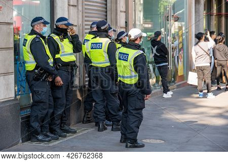 London - May 29, 2021: A Group Of British Police Officers Wearing Ppe Face Masks On A London Street
