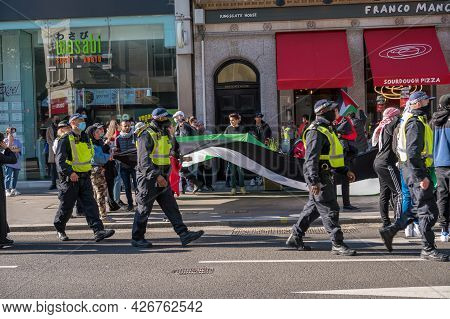 London - May 29, 2021: British Police Officers Walk Alongside Protesters At A Freedom For Palestine